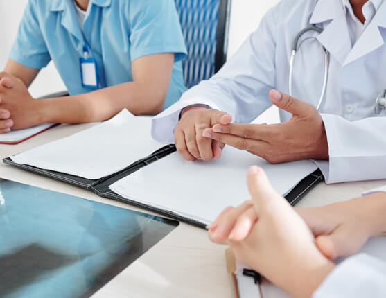 Doctors around table discussing patient file
