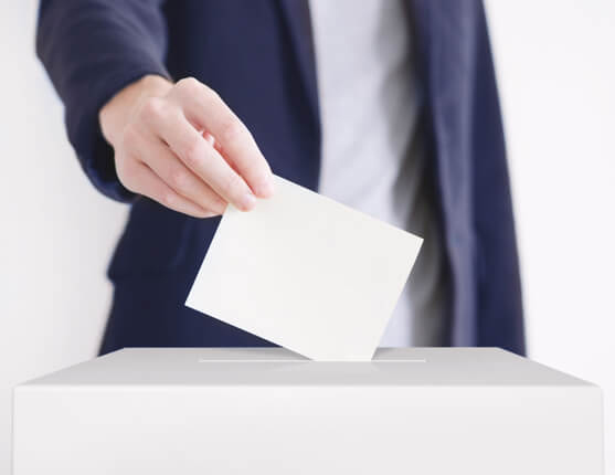 person dropping ballot in box
