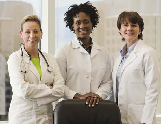 Three women doctors in lab coats smiling at camera