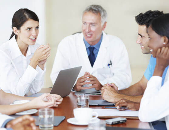 Doctors talking to each other around a table